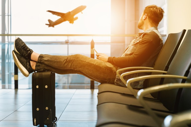 Man waiting in airport looking at a plane