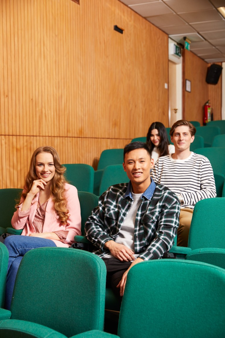 Karolina Rodak, Jessica Tinkler, Daniel Wong & Will Towning in a lecture theatre on a shoot for Regents University